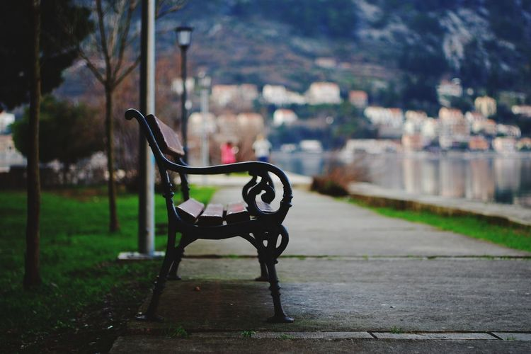 Empty bench in park against buildings in city