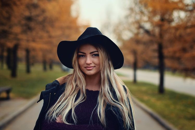 Autumn Beautiful Woman Beauty Blond Hair Casual Clothing Day Focus On Foreground Front View Headshot Leisure Activity Lifestyles Long Hair Looking At Camera Nature One Person Outdoors Park - Man Made Space Portrait Real People Smiling Standing Tree Women Young Adult Young Women