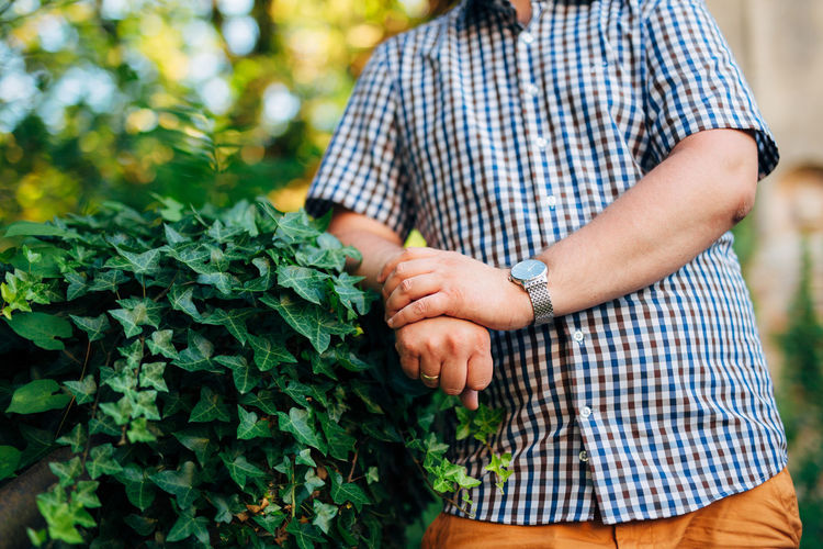 Midsection of man standing near plants