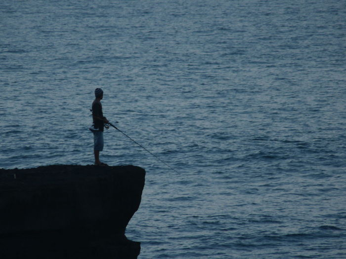 Silhouette Man On Cliff Fishing In Sea