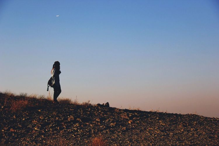 Side view of woman walking on mountain against clear sky during sunset