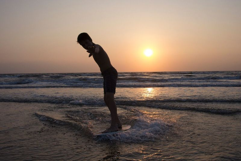 Shirtless Boy Surfing In Sea Against Sky During Sunset