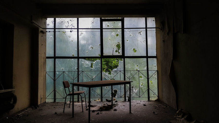 Table and empty chair in abandoned office in front of big window with broken glass