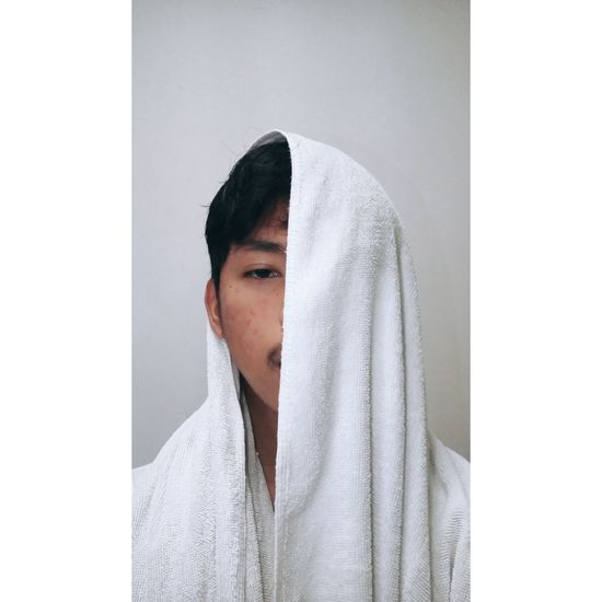 Portrait of man with face covered by towel against gray background