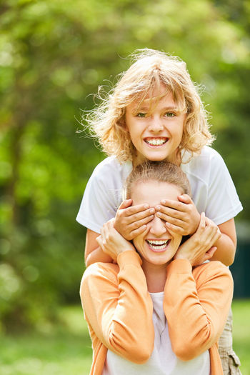 Portrait Of Smiling Daughter Covering Eyes Of Mother On Field