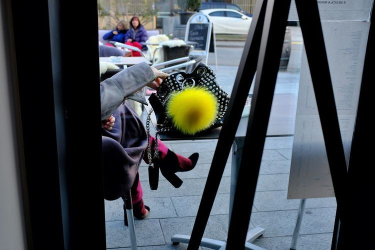 Midsection of woman with umbrella on glass window