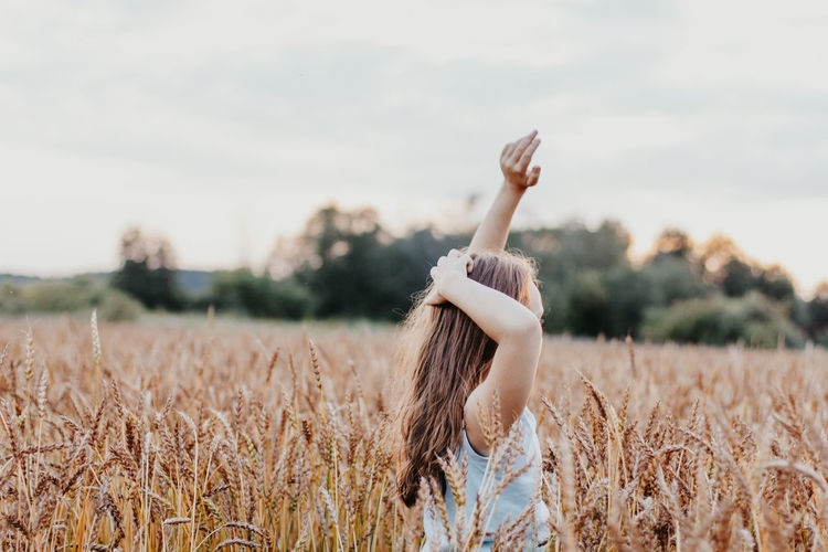 Side view of girl on wheat field during sunset