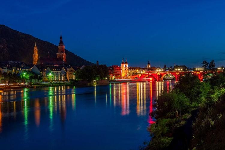 Illuminated bridge over river against blue sky at night