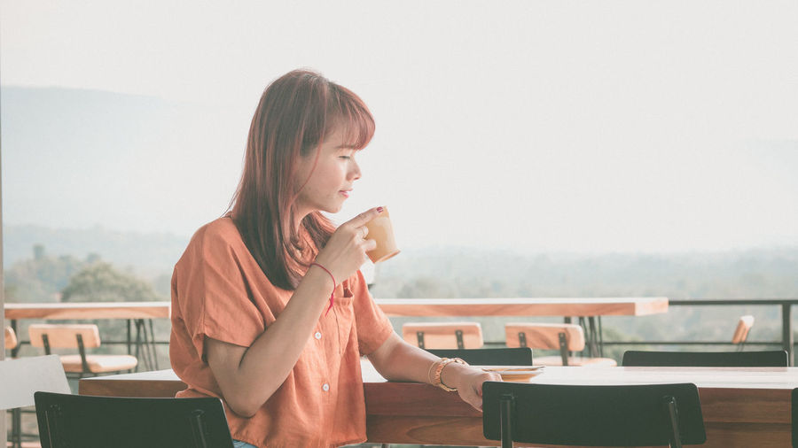 Woman drinking coffee in cup on table against sky