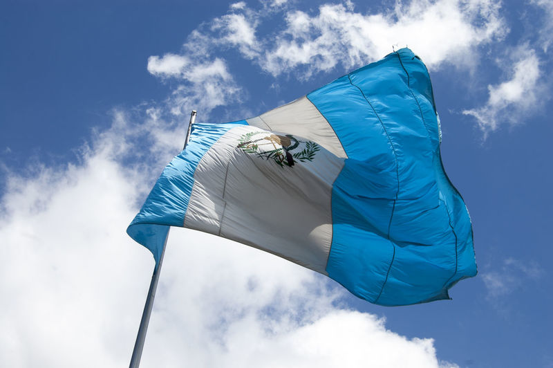 Low angle view of guatemalan flag waving against sky