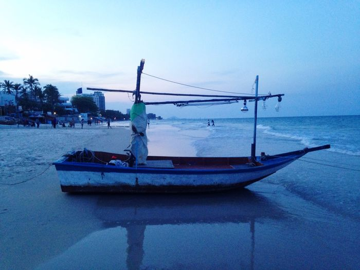 Fishing boat moored on beach against sky