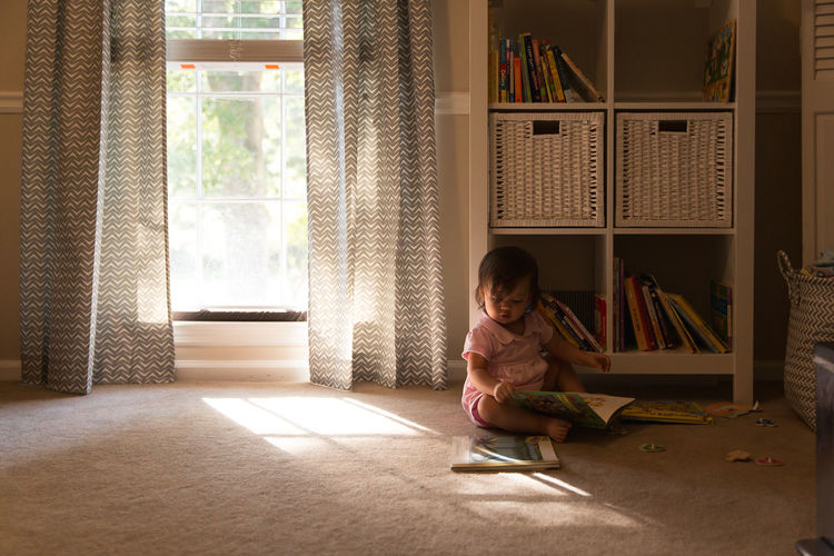 Girl sitting on book at home