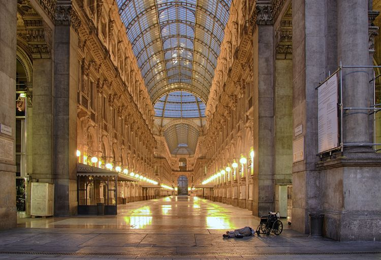Handicapped Man Lying By Wheelchair At Galleria Vittorio Emanuele Ii