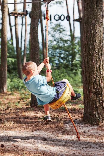 Full length of boy on swing in playground