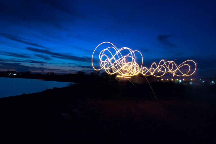 Night Illuminated Long Exposure Light Painting Motion Glowing Blurred Motion Sky Light Trail Wire Wool Creativity Nature Speed Spinning Light - Natural Phenomenon No People Abstract Arts Culture And Entertainment Cloud - Sky Blue Outdoors Dark Sparks Light Firework