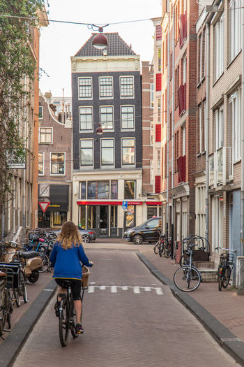 Amsterdam Cyclist Netherlands Architecture Bicycle Building Exterior Built Structure City City Life City Street Cycling Dutch Houses Holland Leaning Houses Mode Of Transportation One Person Outdoors Real People Rear View Ride Riding Tourist Destination