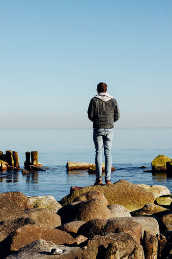 Full length rear view of man standing on rocks by sea against clear sky