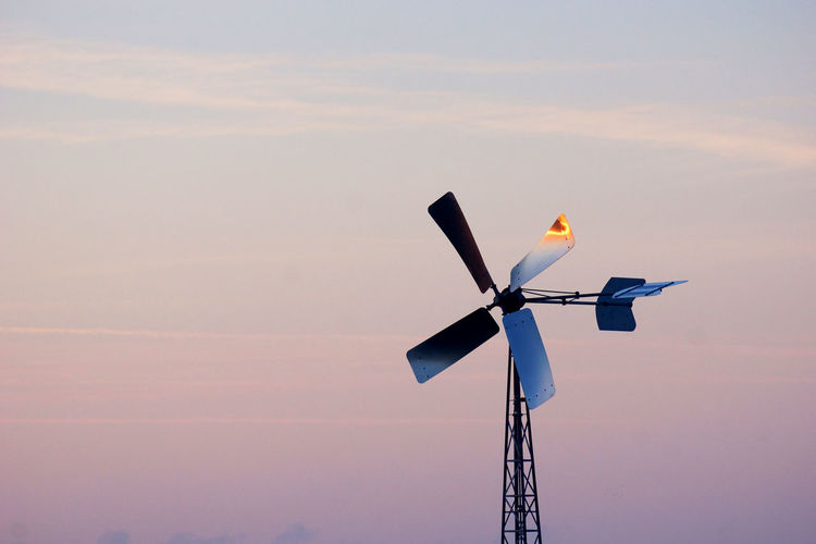 Low angle view of wind turbine against sky during sunset