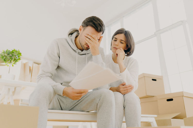 Woman sitting with stressed man by boxes at home
