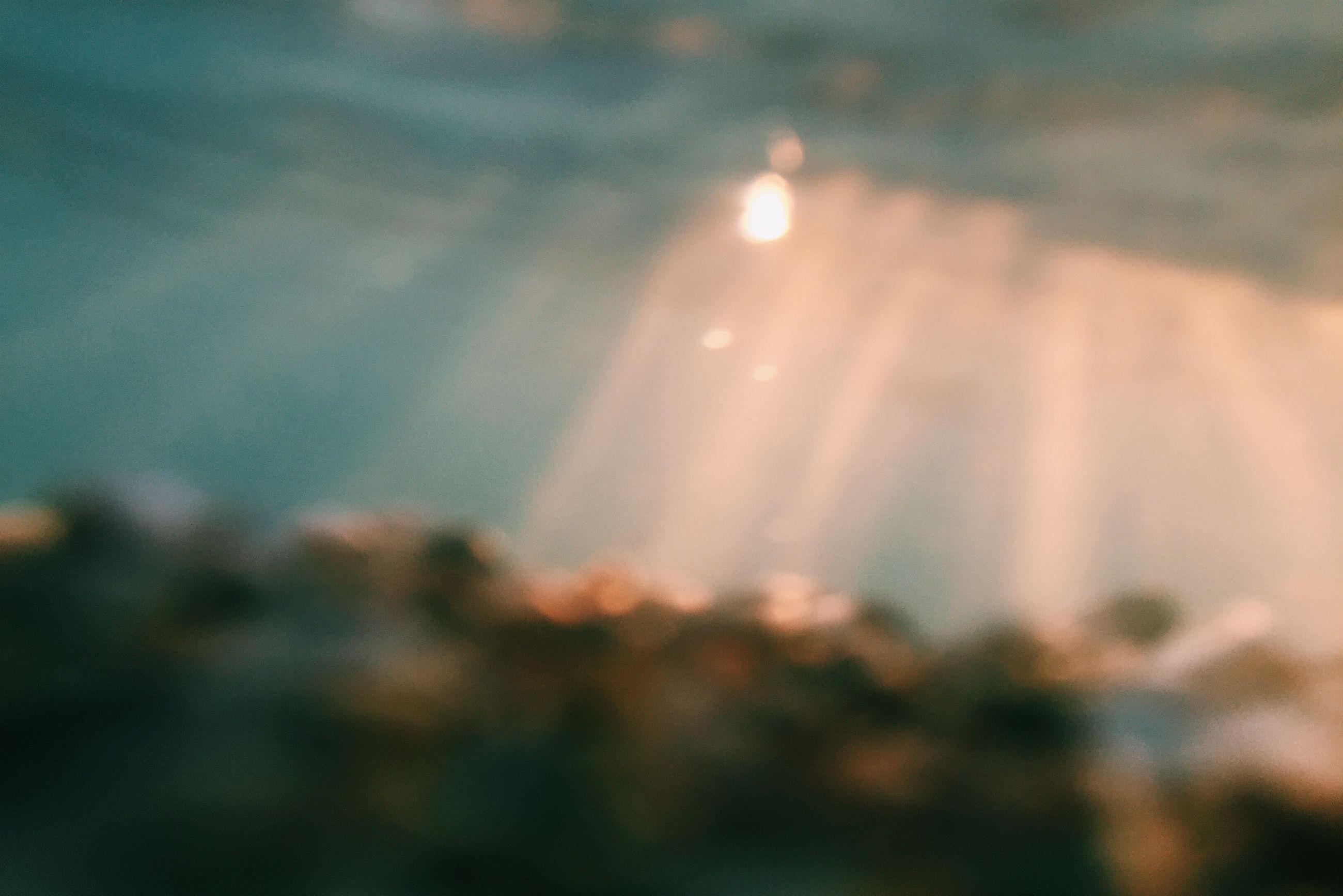 illuminated, defocused, selective focus, lens flare, focus on foreground, sky, night, sunset, outdoors, dusk, light - natural phenomenon, no people, close-up, city, lighting equipment, building exterior, sunlight, street, glowing, cloud - sky