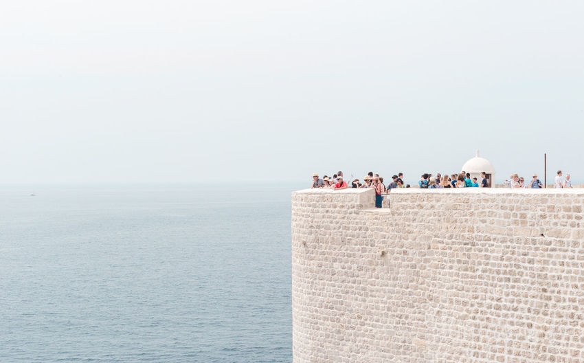 People At Fort Over Adriatic Sea Against Sky