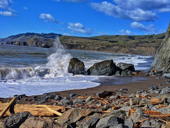 Crashing waves on Boulder on shore. Driftwood foreground. Highland background. Crashing Waves White Boulders Driftwood Rocks Headlands Blue Sky Foreground Background Water Wave Sea Beach Sand Sky Horizon Over Water Landscape Cloud - Sky Rocky Coastline Seascape Shore Rushing Surf Tide Low Tide Coastline Ocean Coastal Feature