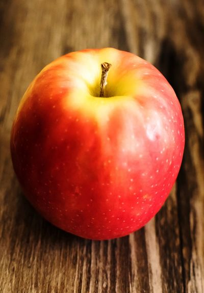 Pink lady apple against wood grain backdrop EyeEm Food Lovers Pink Lady Pink Color Food And Drink Fruit Food Red Healthy Eating Close-up Freshness No People Table Apple - Fruit Indoors  Growth Day