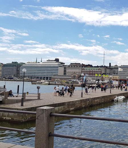 People by buildings in city against sky