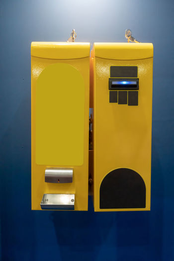 Close-up of yellow mailbox on wall