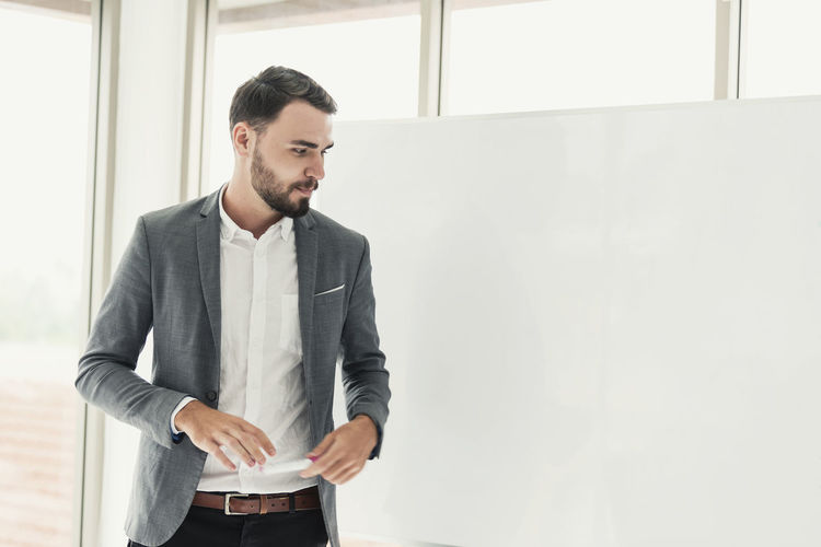 Businessman looking away while standing by whiteboard in office