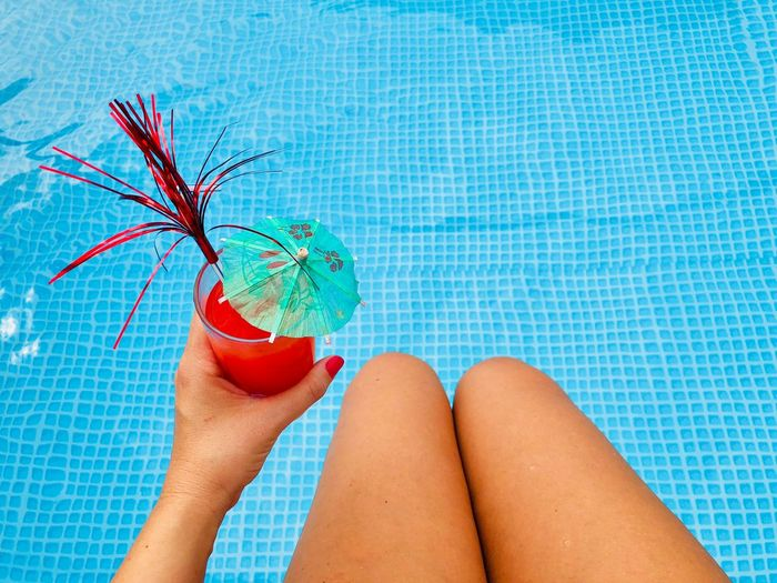 Woman's hand with red nails holding a glass of red orange juice with a small umbrella and a funny straw over the turquoise water of the pool Body Part Relax Vacation Holiday Tanned Legs Feet Umbrella Straw Vitamins Blood Orange Orange Cocktail Fresh Smoothie Juice Refreshment Beverage Cold Drink Drink Glass Red Nails Hold Hand Woman Water Pool Edge Poolside Summer