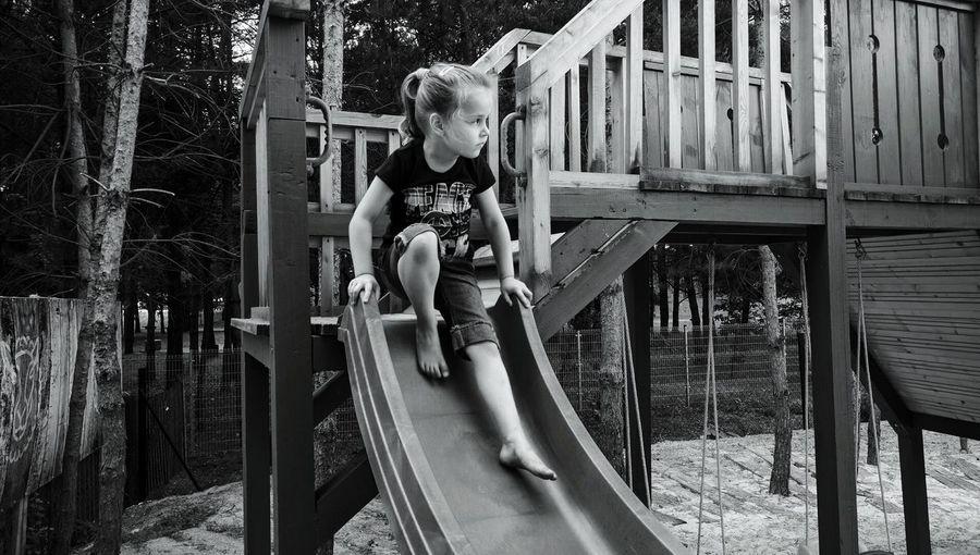 Girl Playing On Slide At Playground