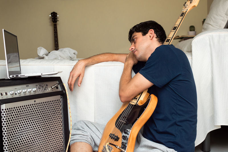 Man playing guitar on bed
