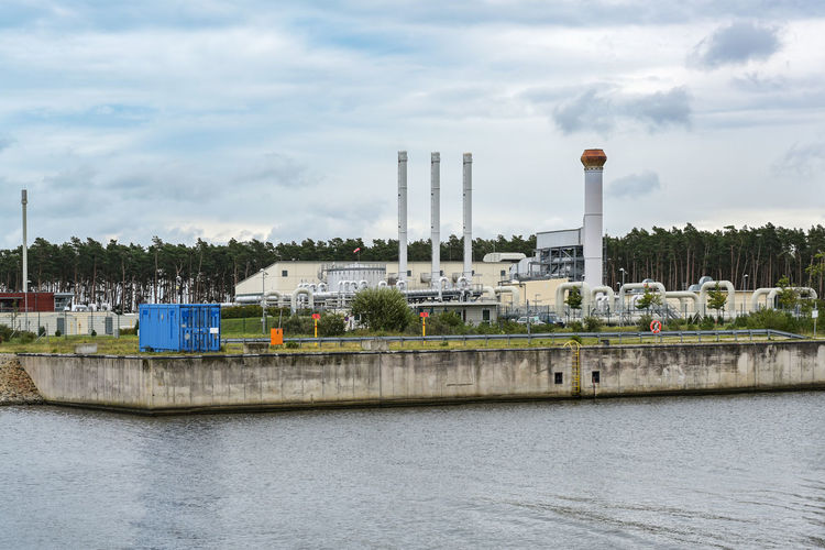 Factory by river against sky