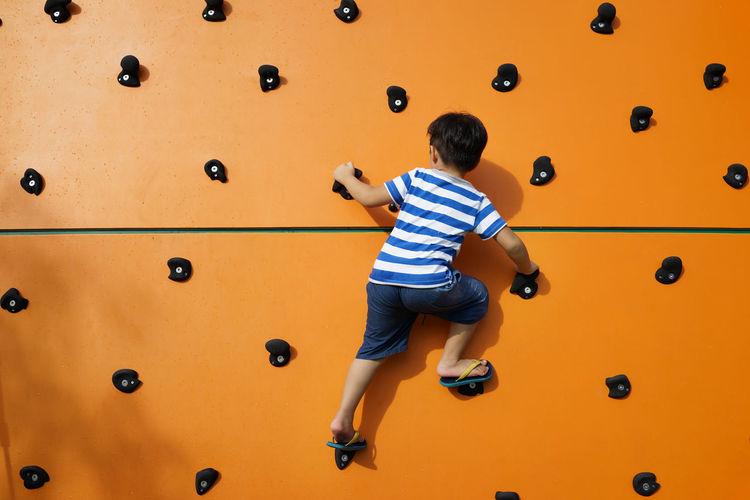 Rear view of boy climbing wall