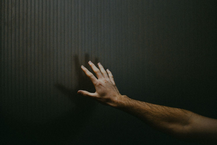 Close-up of cropped hand on wall