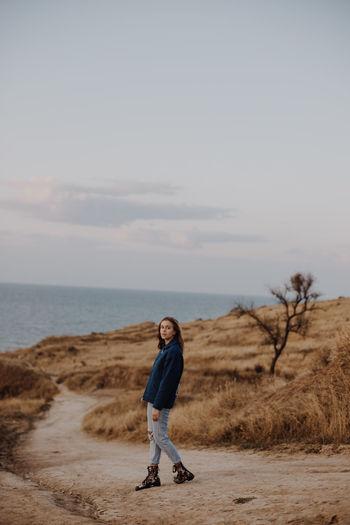 Full length of woman walking on dirt road against sky