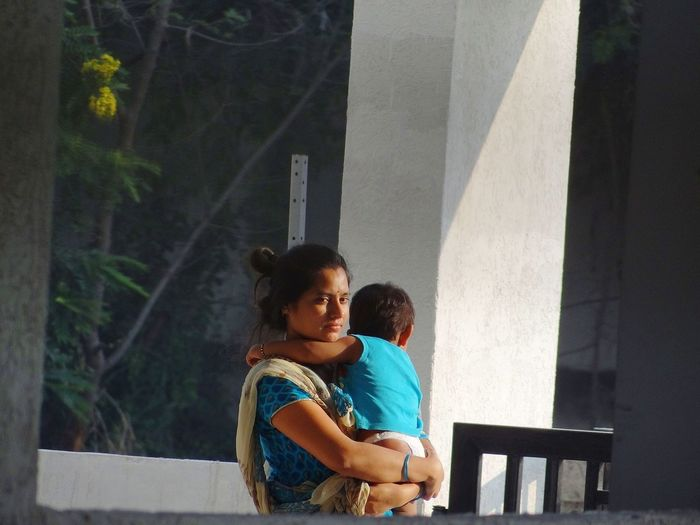 Thoughtful Woman Carrying Child While Standing On Balcony