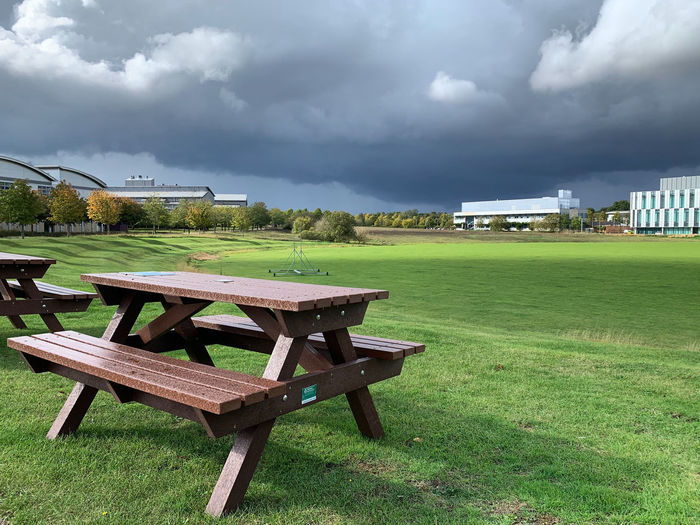 Empty chairs and table on field against sky