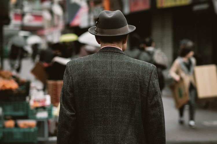 Rear view of man wearing hat and coat while standing on street