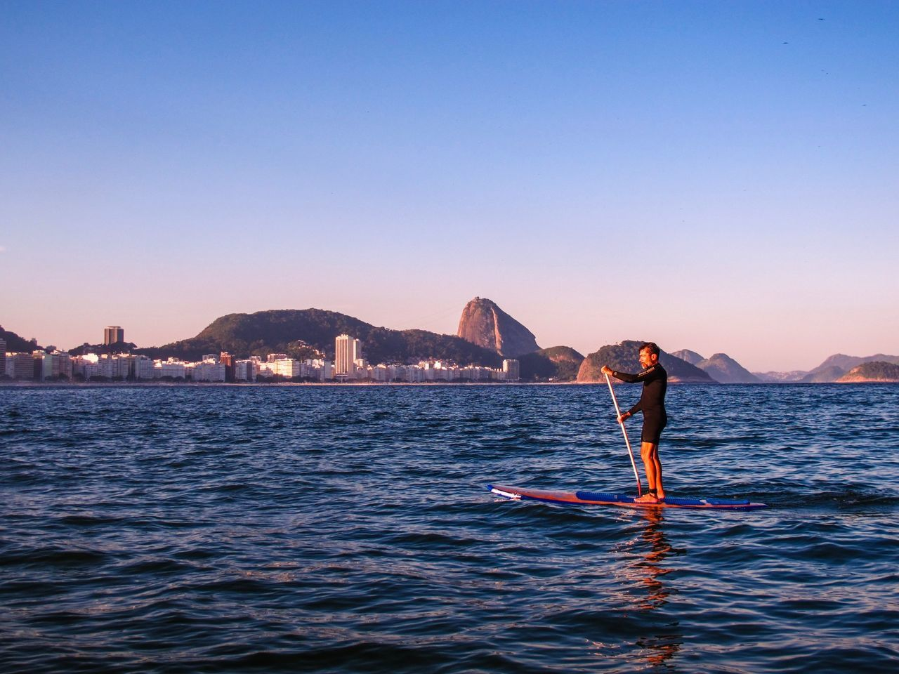 Full Length Of Man Paddleboarding In Sea Against Clear Sky
