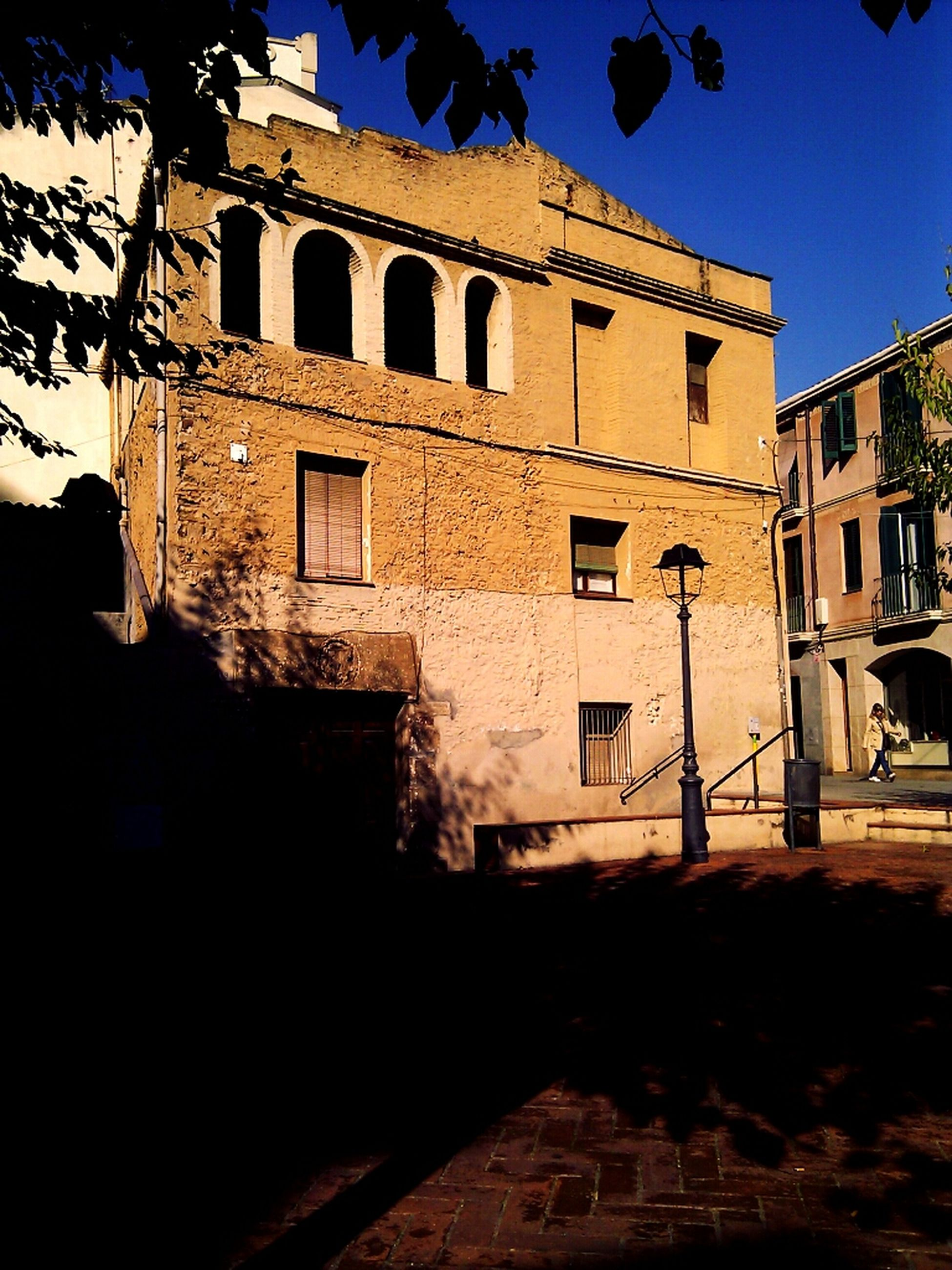 architecture, built structure, building exterior, history, window, building, low angle view, old, residential building, residential structure, arch, sky, clear sky, old town, shadow, sunlight, facade, historic, day, house