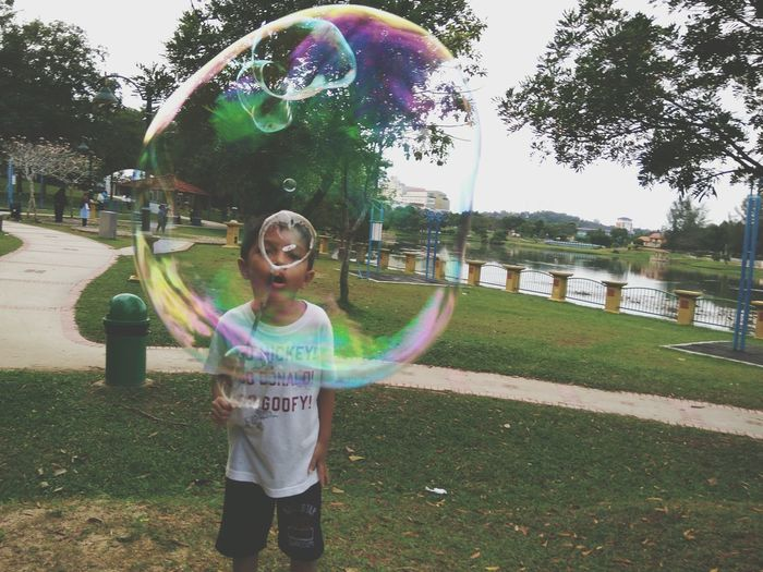 A boy blowing giant bubble. Multi Colored Fun Bubble Motion Child Celebration Outdoors Standing Grass Playing Real People People Childhood Tree One Person Day Cheerful Excitement Fun Holiday Skills  Kids Ful L Length Party - Social Event Adapted To The City Uniqueness Live For The Story BYOPaper!