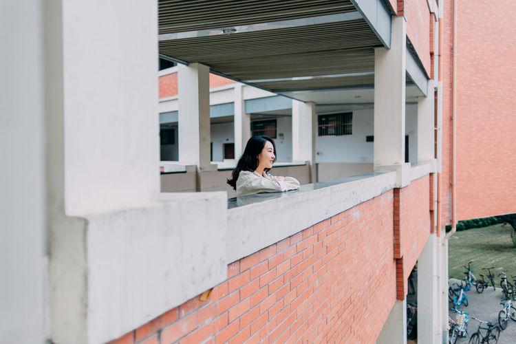 Young woman standing in corridor of building
