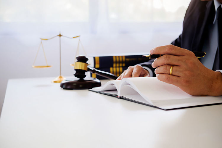Midsection of judge writing in book at table