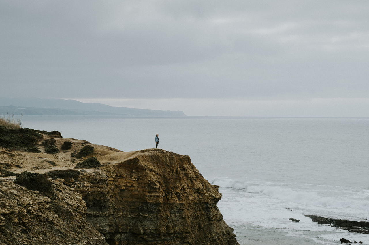 Mid Distance View Of Man Standing On Cliff By Sea