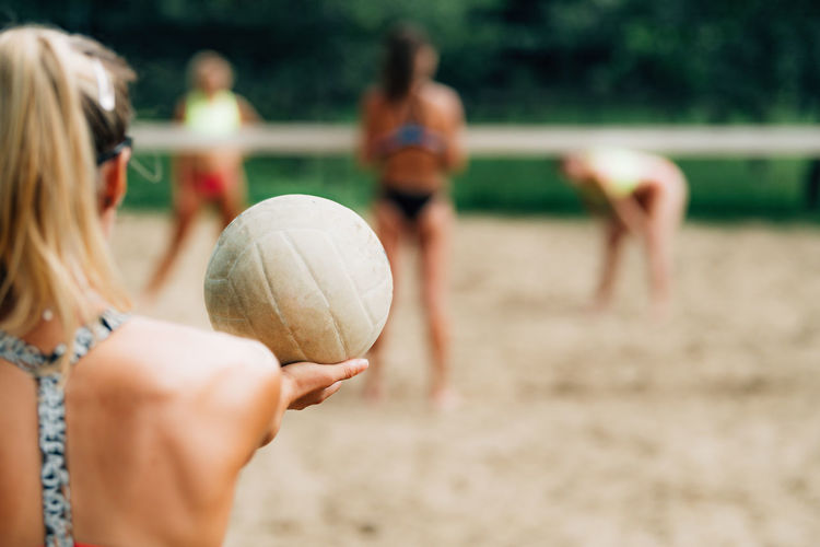 Beach volleyball, female player serving the ball