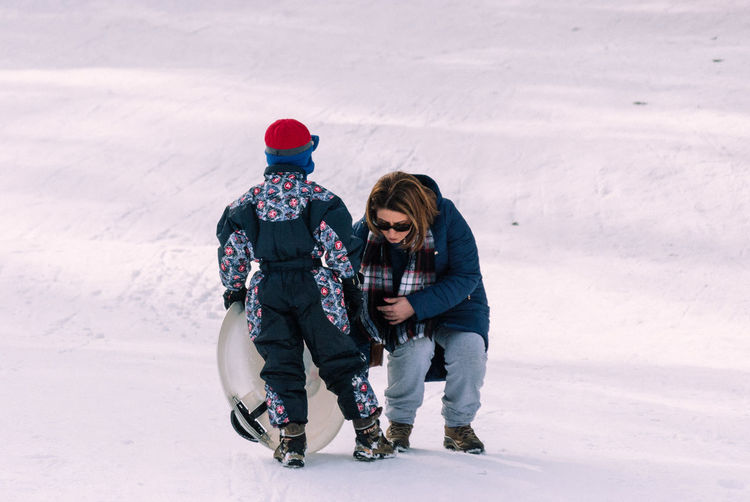 Full length of boy tobogganing by mother on snow