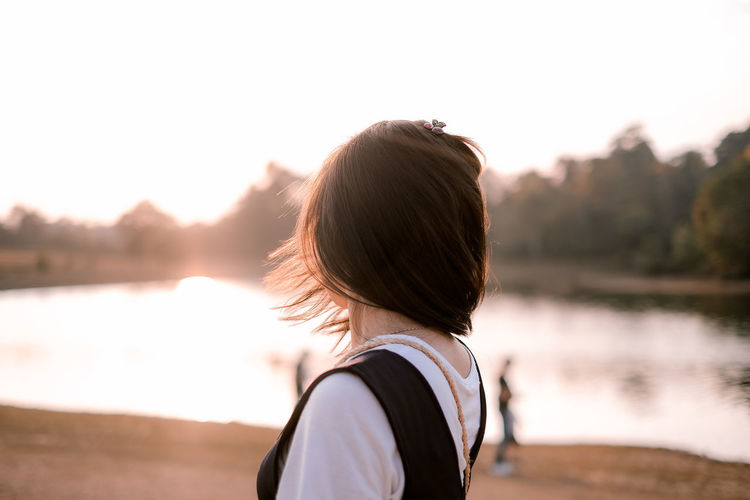 Close-up of woman looking away while standing by lake during sunset