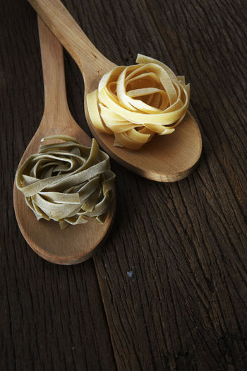 tagliatelle pasta on the wooden table Dried Food Food And Drink Spaghetti Spoon Carbohydrate - Food Type Close-up Directly Above Fettuccine Food Freshness Healthy Eating High Angle View Indoors  Italian Food Kitchen Utensil No People Pasta Raw Food Still Life Studio Shot Table Tagiatelle Variety Wood - Material